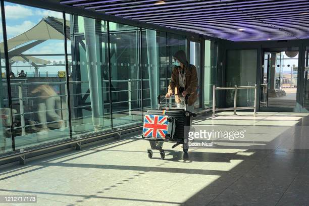 A man wearing a protective mask walks into departures at terminal 5 of Heathrow Airport on March 16 2020 in London England As the coronavirus...