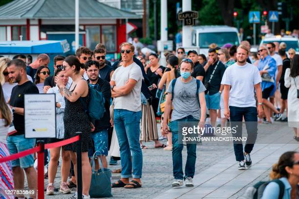 Man wearing a protective mask walks next to travellers as they queue up to board a boat at Stranvagen in Stockholm on July 27 during the novel...