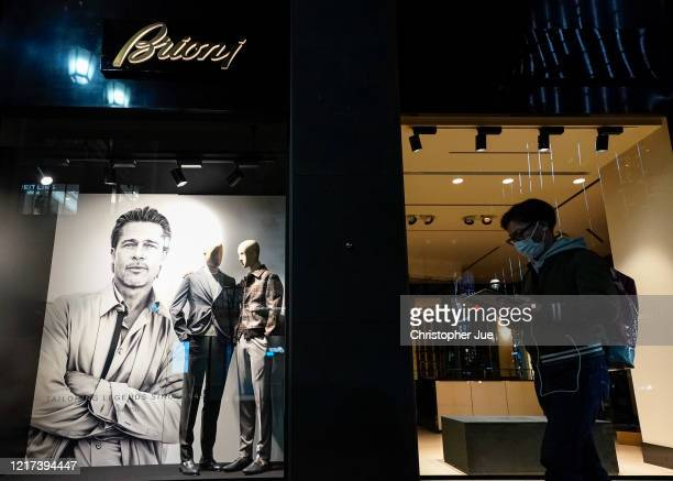 A man wearing a protective mask walks past a luxury menswear company Brioni with US actor Brad Pitt in the advertisement in Tokyo's Ginza district on...