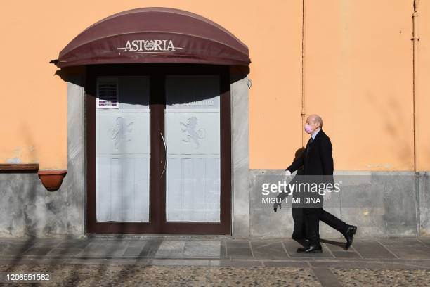A man wearing a protective mask walks past a restaurant in Codogno southeast of Milan on March 11 2020 a day after Italy imposed unprecedented...