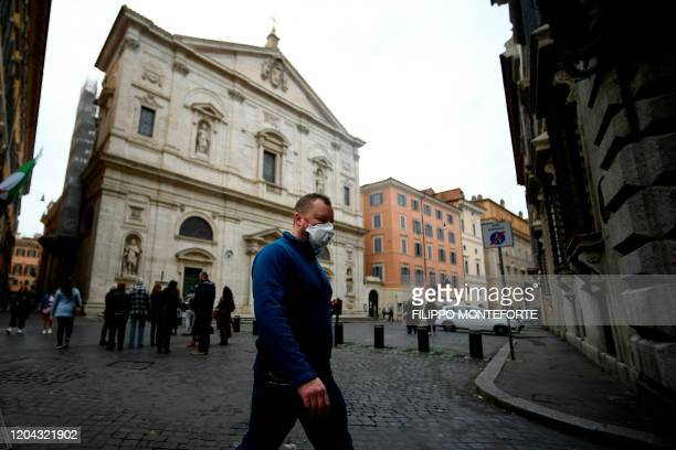 Man wearing a protective mask walks past the Church of St. Louis of the French in Rome on March 1, 2020. - The French community church closed its...