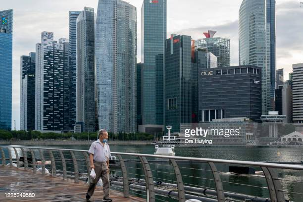 Man wearing a protective mask walks past the Marina Bay Sands Shopping Center with the central business district in the background on July 07, 2020...