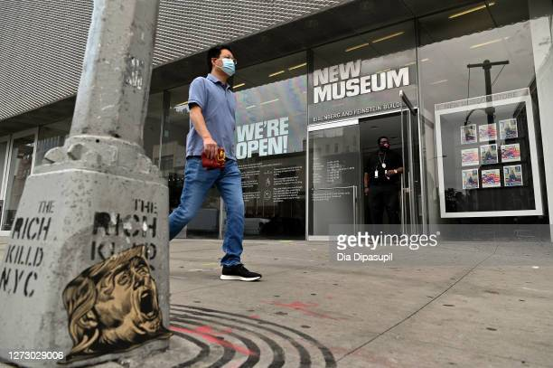 Man wearing a protective mask walks past the newly reopened New Museum of Contemporary Art on Manhattan's Lower East Side as the city continues Phase...