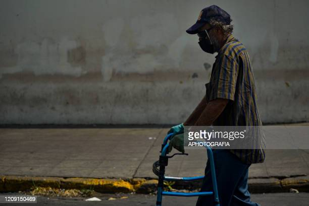 A man wearing a protective mask walks through a street with the help of a walker on April 2 2020 in San Salvador El Salvador On March 21st President...