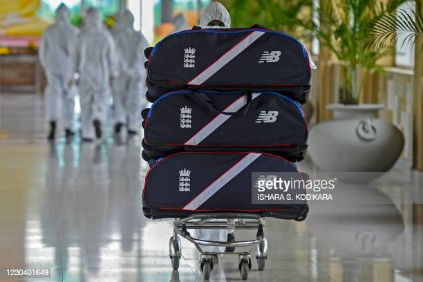 Man wearing a protective suit pushes a trolley loaded with the luggage of England's cricket team upon their arrival at the Rajapaksa international...