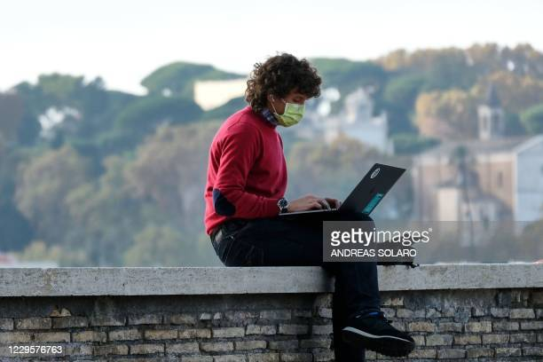 Man wearing a protective surgical mask works on his laptop on a terrace of the Oranges Gardens on Aventine Hill in Rome on November 11 during the...