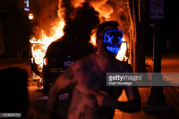 A man wearing a 'Purge' mask runs in front of a burning police car during a protest on May 29 2020 in Atlanta Georgia Demonstrations are being held...