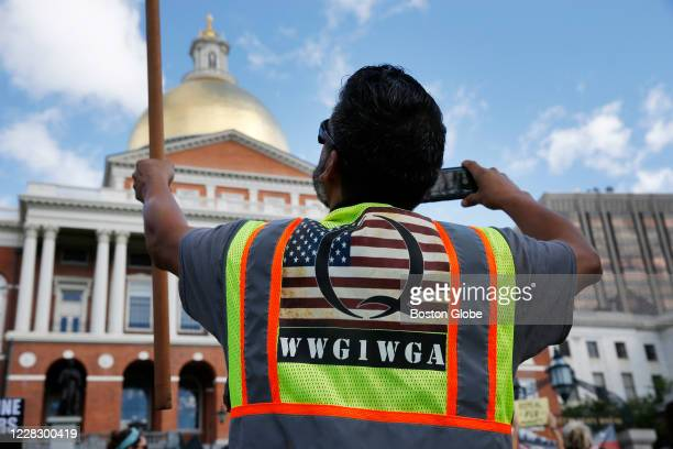 Man wearing a Q Anon vest held a flag during a No Mandatory Flu Shot Massachusetts rally held outside of the State House in Boston on Aug. 30 to...