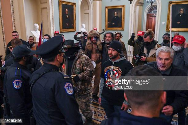 Man wearing a QAnon sweatshirt protests against US Capitol police officers as they try to stop supporters of US President Donald Trump from entering...