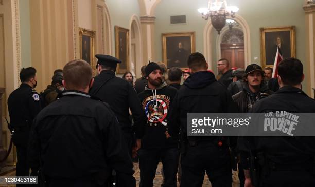 Man wearing a QAnon sweatshirt stands with other protesters, against US Capitol police officers as they try to stop supporters of US President Donald...