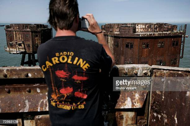 A man wearing a radio Caroline tshirt takes a photo of Redsand towers on June 30 2006 in Whitstable England The Redsand Towers coded 'Uncle 6' during...