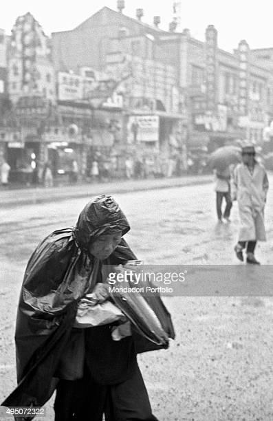 A man wearing a raincoat to protect himself from the rain Hong Kong 1961