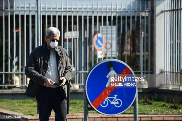 Man wearing a respiratory mask walks outside the municipal hospital in Codogno, southeast of Milan, on February 22, 2020. - Streets were deserted and...