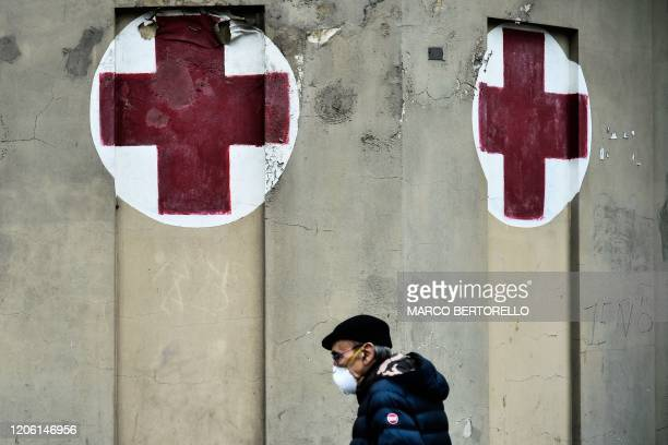A man wearing a respiratory mask walks past the Molinette hospital in Turin on March 9 2020 as Italy is battling the world's secondmost deadly virus...
