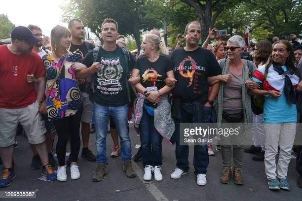 Man wearing a right-wing t-shirt and a couple wearing QAnon shirts face off against riot police on Unter den Linden avenue during protests against...