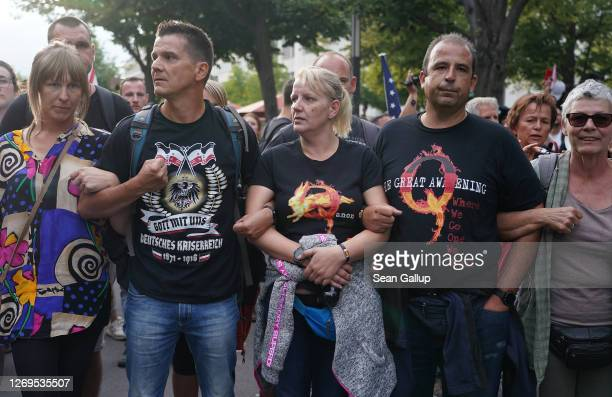A man wearing a rightwing tshirt and a couple wearing QAnon shirts face off against riot police on Unter den Linden avenue during protests against...