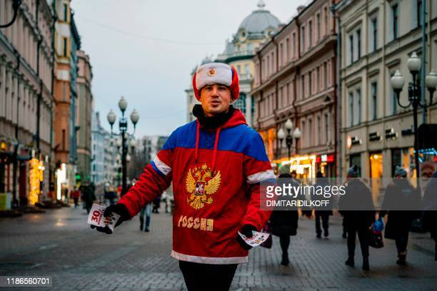 Man wearing a Russian ice hockey jersey distributes leaflets in downtown Moscow on December 5, 2019. - The executive committee of the World...