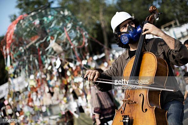 A man wearing a safety helmet and a gas mask plays a cello in Istanbul's Taksim square on June 15 2013 Turkish protesters on Saturday refused to...