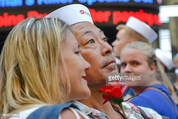A man wearing a sailor's cap and a woman holding a rose pose for a selfie at the TimesSquare kissin To mark the 70th anniversary of the surrender of...