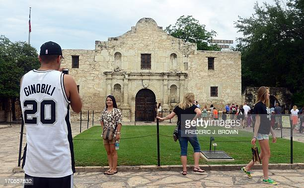 A man wearing a San Antonio Spurs jersey with Manu Ginobili's name on the back snaps a photo of his friend in front of the Alamo on June 14 2013 in...