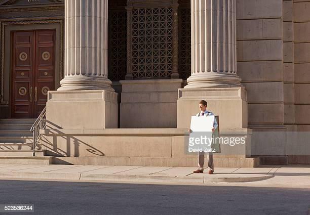 man wearing a sandwich board on the sidewalk - advertising column stock-fotos und bilder