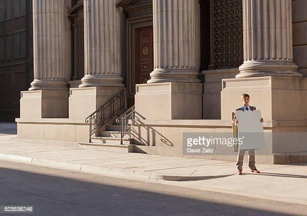 Man wearing a sandwich board on the sidewalk