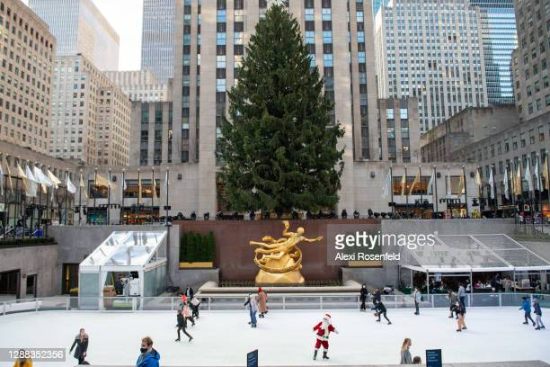 Man wearing a Santa Claus costume skates at The Rink at Rockefeller Center near the newly unveiled Christmas Tree on November 28, 2020 in New York...