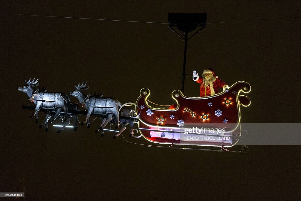 A man wearing a Santa Claus costume waves from his sleigh as he carried over the Champs Elysees avenue in Paris on December 23, 2014 in Paris.