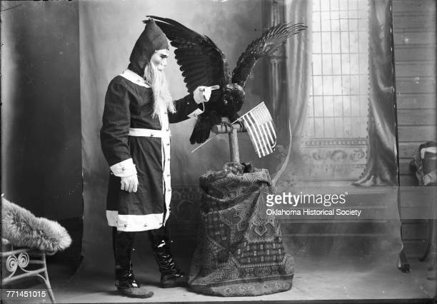 Man wearing a Santa Claus suit and mask, holding his finger out to a stuffed bird of prey, which is holding an American flag, Gray, Oklahoma, circa...