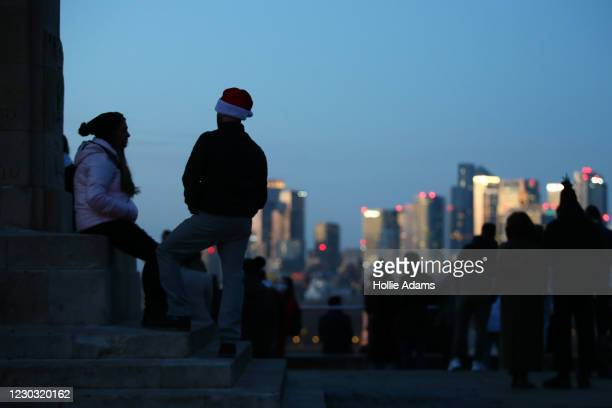 Man wearing a Santa hat watches the sunset over Canary Wharf from the top of Greenwich Park on December 27, 2020 in London, United Kingdom. Last...