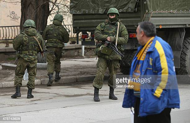 A man wearing a scarf and jacket in the blue and yellow of the Ukrainian flag walks past heavilyarmed soldiers displaying no identifying insignia in...