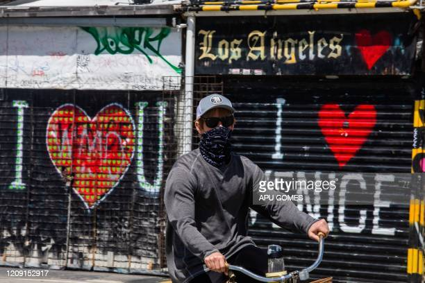 A man wearing a scarf as a facemask rides his bike in Venice Beach on April 4 2020 in Los Angeles California during the coronavirus pandemic US...