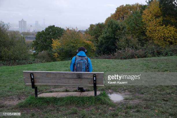 A man wearing a set of headphones over his winter cap sits alone on a bench on Parliament Hill with the backdrop of the city skyline on a Sunday in...