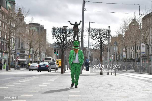 A man wearing a shamrock suit walks along the normally bustling parade route on OConnell Street is quiet following the cancellation of the annual...