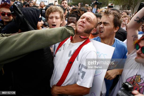 A man wearing a shirt with swastikas on it is punched by an unidentified member of the crowd near the site of a planned speech by white nationalist...