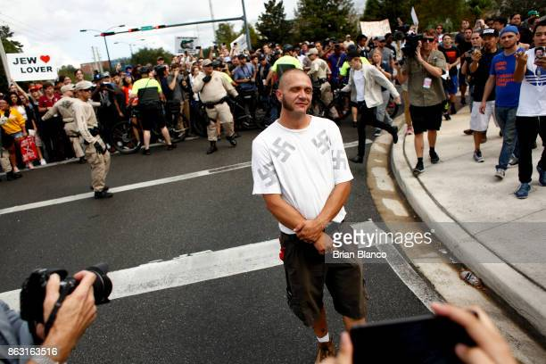 A man wearing a shirt with swastikas walks away moments after being punched by an unidentified member of the crowd near the site of a planned speech...