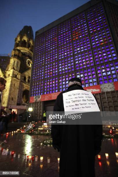 A man wearing a sign that reads 'No Terror' looks at a memorial to victims following the memorial's inauguration at the site of the 2016 Christmas...