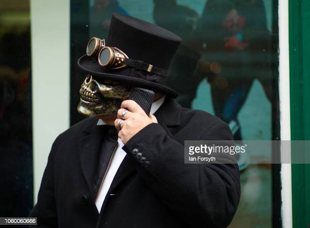 A man wearing a skull mask speaks on his phone during Whitby goth Weekend on October 27 2018 in Whitby England The Whitby goth weekend began in 1994...