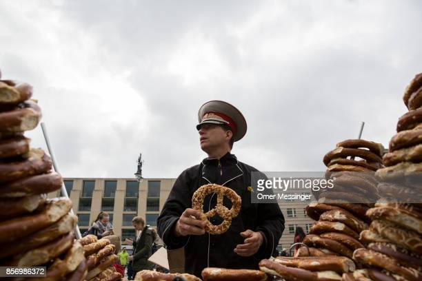 A man wearing a Soviet Military hat is selling pretzels near the Brandenburg Gate on German Unity Day on October 3 2017 in Berlin Germany Unity Day...