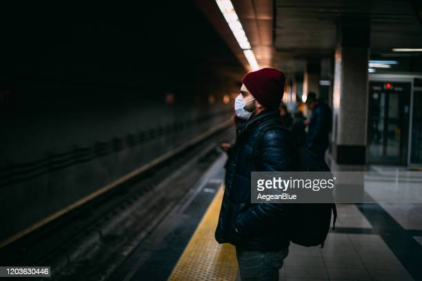 man wearing a sterile mask in the subway - swine influenza virus stock pictures, royalty-free photos & images