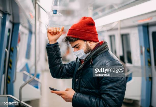 man wearing a sterile mask in the subway - face masks imagens e fotografias de stock