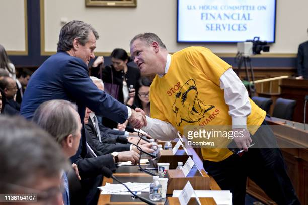 A man wearing a 'Stop Loan Sharks' tshirt shakes hands with Brian Moynihan chief executive officer of Bank of America Corp during a House Financial...
