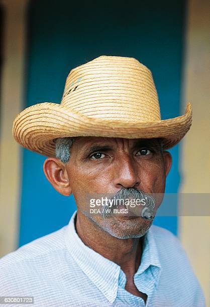 A man wearing a straw hat and smoking a cigar Havana Cuba