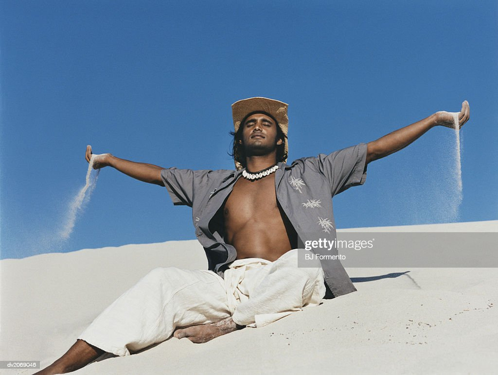 Man Wearing a Straw Hat Sits in the Sand With His Arms Out and Eyes Closed : Stock Photo