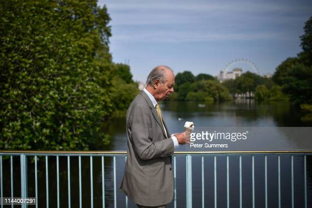 A man wearing a suit eats an ice cream as he walks through St James's Park on May 15 2019 in London England Forecasters are predicting days of hot...