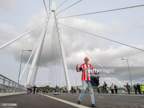 A man wearing a Sunderland Football Club shirt gestures as he walks across new Northern Spire bridge spanning the River Wear as it opens for a...