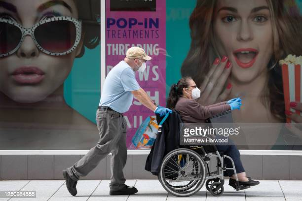 Man wearing a surgical face mask pushes a woman in a wheelchair past shops on Queen Street on June 19, 2020 in Cardiff, United Kingdom. The First...