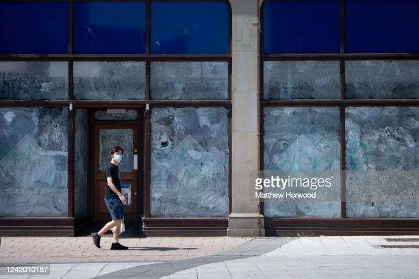 Man wearing a surgical face mask walks passed a closed-down shop on June 2, 2020 in Cardiff, United Kingdom. The Welsh government has further relaxed...