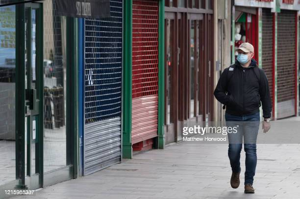 Man wearing a surgical face mask walks passed closed shops on March 31, 2020 in Cardiff, United Kingdom. The Coronavirus pandemic has spread to many...