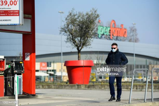 A man wearing a surgical mask walks past a petrol station in Codogno southeast of Milan on February 22 2020 Streets were deserted and residents...